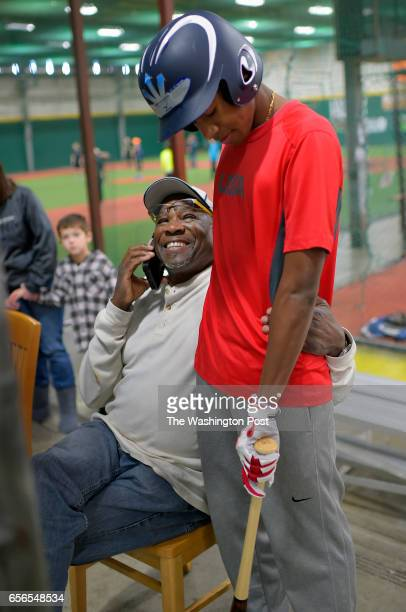 New Washington Nationals manager Dusty Baker left has his arm around his 16 year old son Darren as they wit for a batting cage to open up near his...