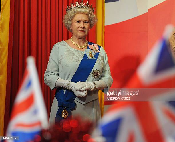 A new waxwork statue of Britain's Queen Elizabeth II stands as children from Norbreck primary school have a Diamond Jubilee party at Madame Tussauds...