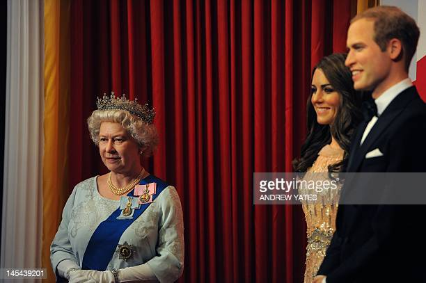 A new waxwork statue of Britain's Queen Elizabeth II stands next to a statue of Catherine Duchess of Cambridge and Prince William as children from...