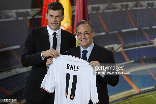 New Welsh striker Gareth Bale of Real Madrid poses with his new jersey next to Real Madrid's President Florentino Perez during his presentation at...