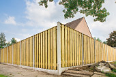 New wooden fence as corner around garden of home. In the netherlands I took this photo of an enclosure surrounding a back garden. People often build such an inclosure to protect their garden against u