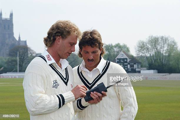 New Worcestershire signings Graham Dilley and Ian Botham with a mobile phone during the pre season photocall at New Road on April 1 1987 in Worcester...