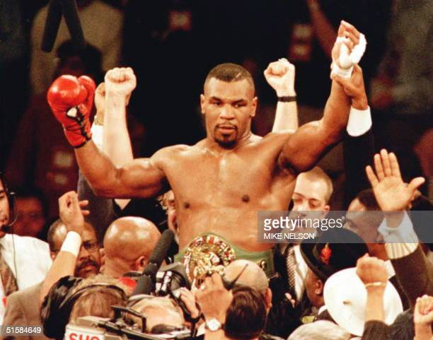 New World Boxing Council heavyweight champion Mike Tyson is lifted into the air wearing the championship belt after defeating WBC heavyweight...