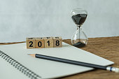 new year 2018 goals, target or checklist concept as number 2018 wooden cube block with sandglass and white paper note with pencil on wooden table.