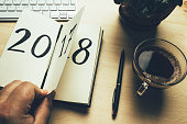 New Year 2018 is coming concept. Hand flips notepad sheet on wooden table. 2017 is turning, 2018 is opening, retro toned