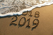 New year 2019 and old year 2018 written on sandy beach with waves