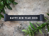 'Happy New Year 2019' wording written on ripped black paper. On background of wooden table.