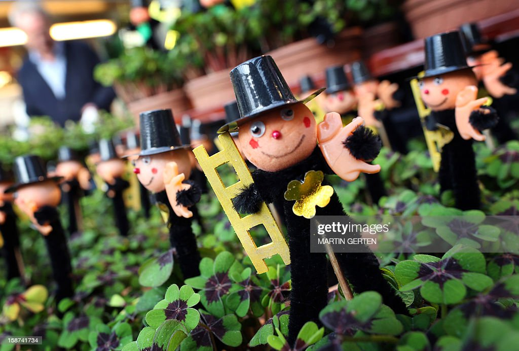 New Year gifts, small chimneysweep figures sticking in four-leaved clover, are for sale in Duesseldorf, western Germany, on December 27, 2012. Chimneysweeps and four-leaved clover are considerated as lucky charms in Germany. AFP PHOTO / MARTIN GERTEN GERMANY OUT