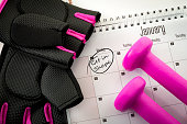 New year resolution and the desire to get in shape concept with a calendar with january first circled, gym equipment like purple dumbbells and pink and black workout gloves