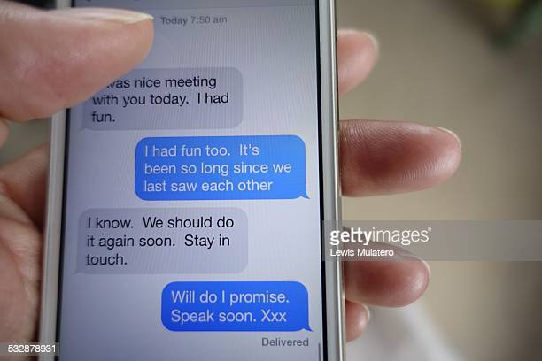 New year resolution to stay in contact with friends family and relatives Close up of female hand holding mobile phone with text messages promising to...