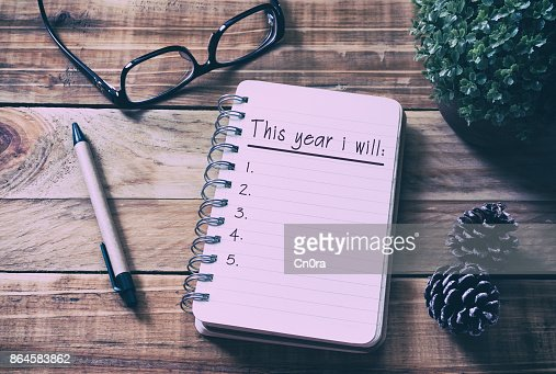 New Year Resolutions List on Notepad on Top of Wood Desk : Foto de stock