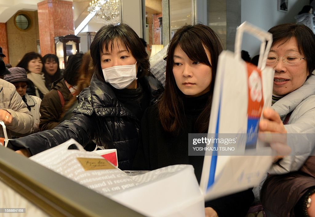 New Year shoppers pick up 'lucky bags' containing items worth three times as much as their price tag to celebrate the New Year business at a department store in Tokyo on January 2, 2013. Lucky bags are sold to celebrate the New Year business, Japan's biggest holiday of the year. AFP PHOTO / Yoshikazu TSUNO