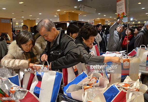 New Year shoppers pick up 'lucky bags' containing items worth three times as much as their price tag during the annual event to celebrate the New...