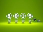 2015 New Year sign inside light bulbs on green background