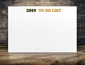 2019 new year to do list on white paper poster on brown wood floor room and brick wall,Business vision mock up for adding your list