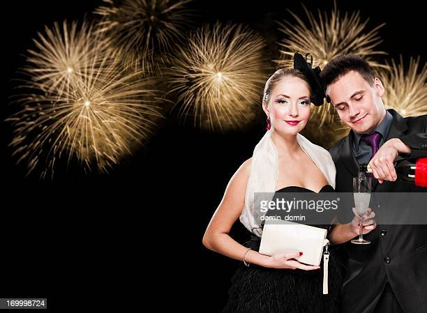 New Year's couple with glass of champagne against fireworks, night