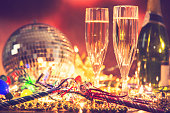 New Year's Eve holiday party with sparkling wine, disco ball, decorations.