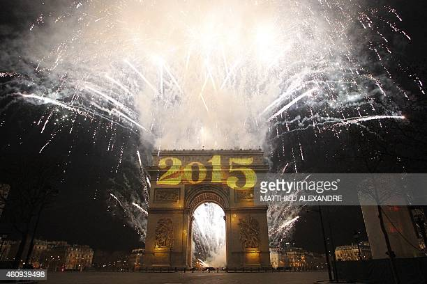 New Year's fireworks erupt over the Arc de Triomphe on the ChampsElysees at midnight on January 1 2015 AFP PHOTO / MATTHIEU ALEXANDRE
