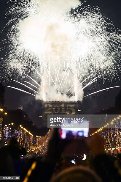 New Year's fireworks erupt over the crowd at ChampsElysees in Paris France on January 01 2015