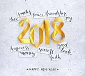New Year's handwritten wishes on strips of white paper lying on a concrete background. Square composition with gold paper strips bent in 2018 shape. Beautiful and original design.