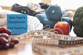 New year's resolution to get healthy in the coming year!  Group of objects includes:  note, fruit, tape measure,ear buds, athletic shoes, dumbbells, water bottle and towel.   Concept of an individual