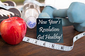 """New Year's Resolution to get healthy in January of the coming year.  Image features: dumbbells, sports shoes, water bottle, apple, towel, tape measure on wooden table.  Adhesive note reading """"New Year"""