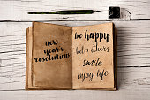 high angle view of a notepad with some new years resolutions written in it, such as be happy, help others, smile or enjoy life, a nib pen and a bottle of writing ink on a rustic white wooden table