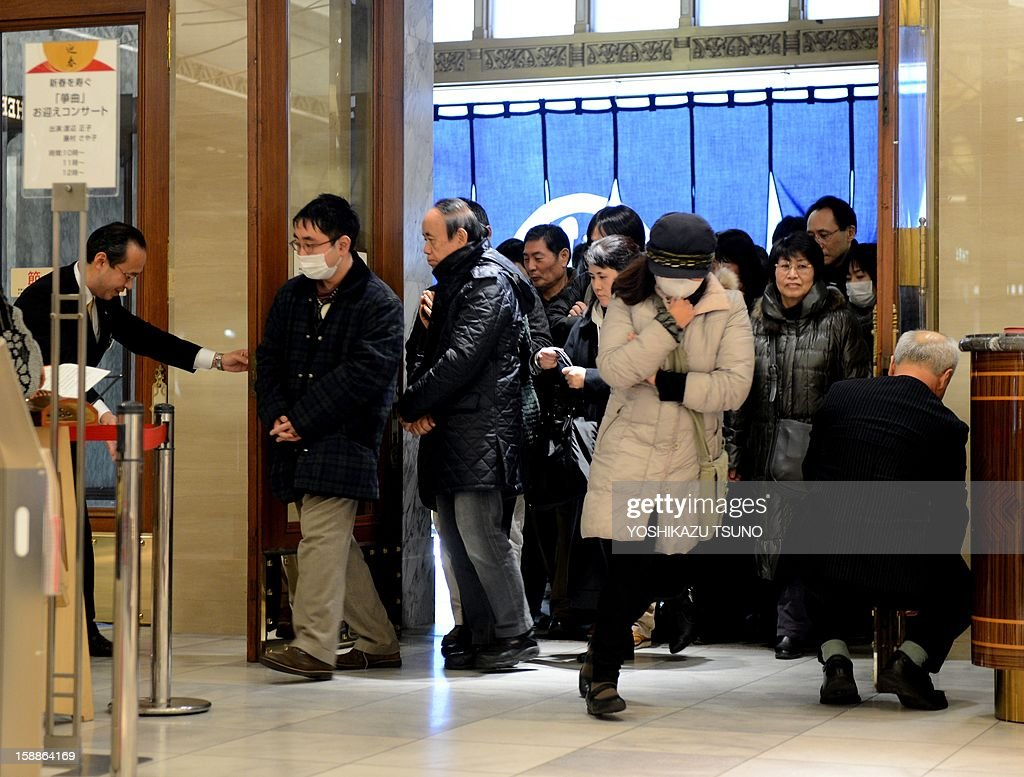 New Year's shoppers rush into a Mitsukoshi department store to buy 'lucky bags' containing items worth three times as much as their price tag to celebrate the New Year business in Tokyo on January 2, 2013. Lucky bags are sold to celebrate the New Year business, Japan's biggest holiday of the year. AFP PHOTO / Yoshikazu TSUNO