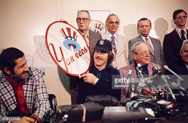 At Yankee Offices across the street from Shea Stadium Jim 'Catfish' Hunter holds Yankee emblem after signing multimillion dollar contract with the...