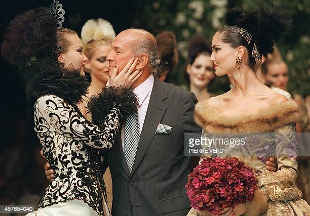 New York based Santa Dominican designer Oscar de la Renta gets a kiss from one of his models as his bride's model looks on 09 July in Paris at the...