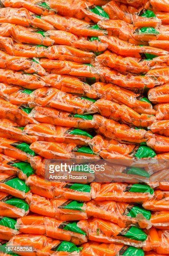 USA, New York, Brooklyn, Stack of plastic bags packed with carrots : Stock Photo