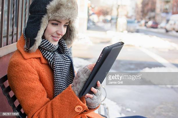 USA, New York, Brooklyn, Woman on bench in street using tablet