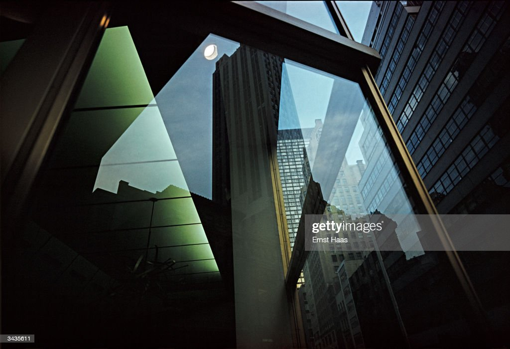 New York buildings and their reflections viewed through a revolving door. Image Appears - America !