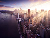 New York City - beautiful colorful sunset over manhattan with sunbeams between buildings