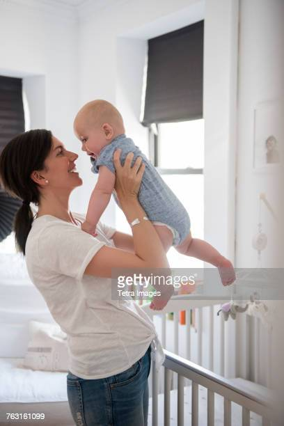 New York City, Brooklyn, Mother holding baby boy (6-11 months) in nursery