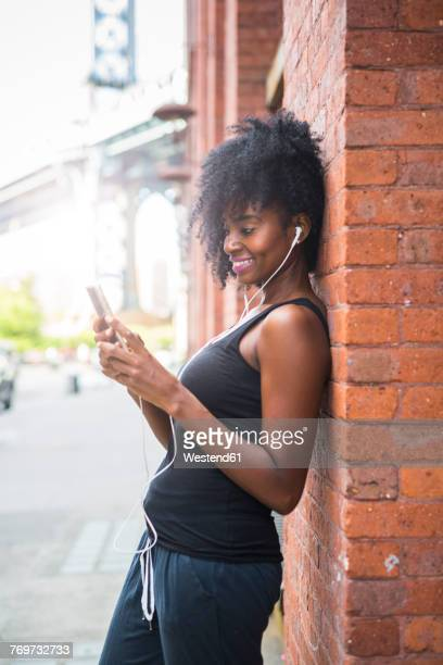 USA, New York City, Brooklyn, smiling woman leaning against brick wall listening to music