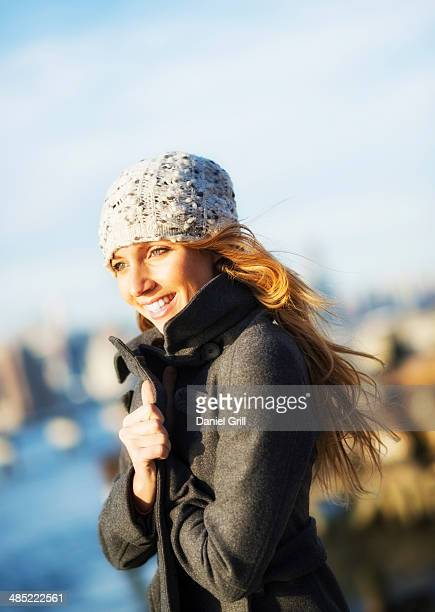 USA, New York City, Brooklyn, Williamsburg, Portrait of cheerful woman in overcoat in autumn