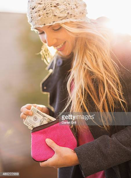 USA, New York City, Brooklyn, Williamsburg, Portrait of woman holding purse with banknotes