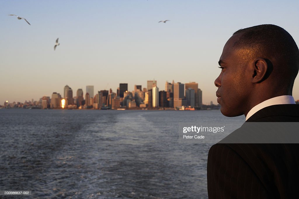 USA, New York City, business man looking at view of Manhattan from water : Stock Photo