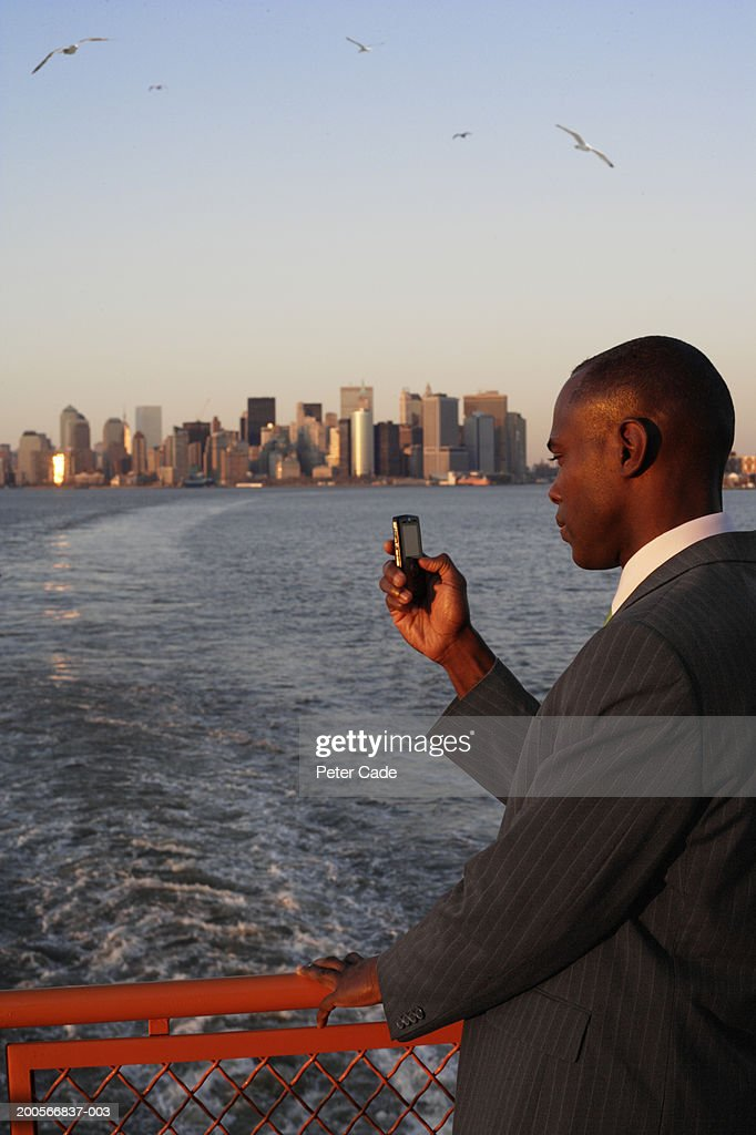 USA, New York City, business man using mobile phone on ferry with view of Manhattan : Stock Photo