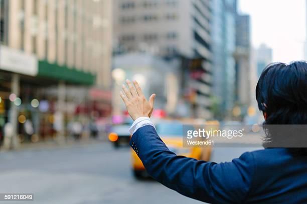 USA, New York City, businessman hailing a taxi