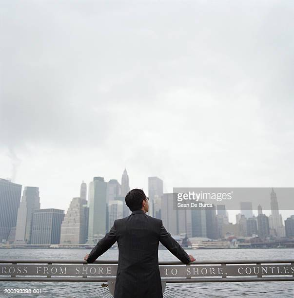 USA, New York City, businessman looking at skyline, rear view