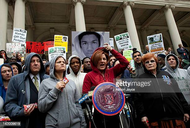 New York City Council Speaker Christine Quinn puts on a hoodie as she speaks during a press conference to call for justice in the February 26 killing...