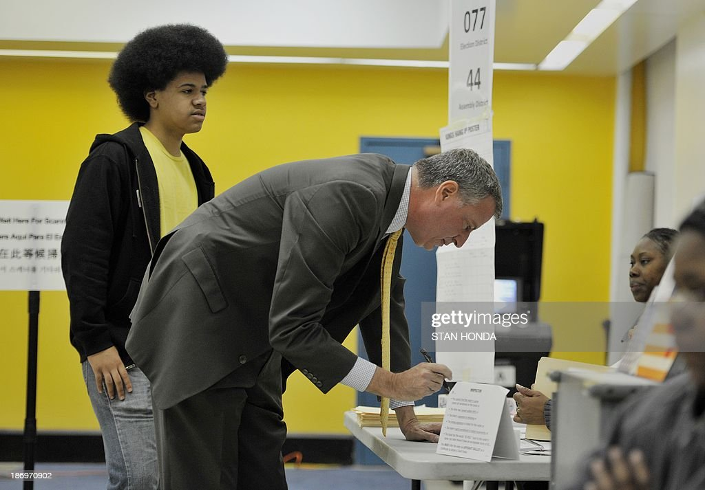 New York City Democratic mayoral candidate Bill de Blasio prepares to vote with son Dante (L) at the Park Slope Branch Public Library in the Brooklyn borough of New York November 5, 2013. AFP PHOTO/Stan HONDA