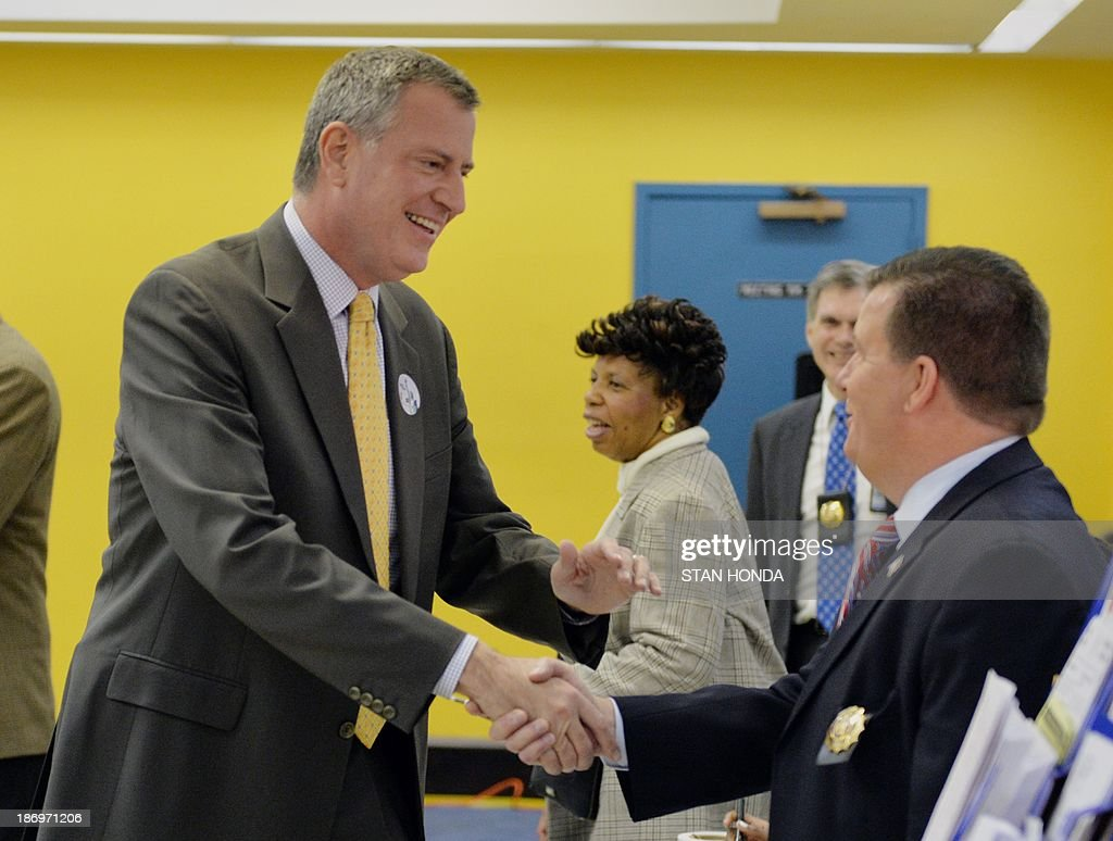 New York City Democratic mayoral candidate Bill de Blasio (L) shakes hands with an election official after voting at the Park Slope Branch Public Library in the Brooklyn borough of New York November 5, 2013. AFP PHOTO/Stan HONDA
