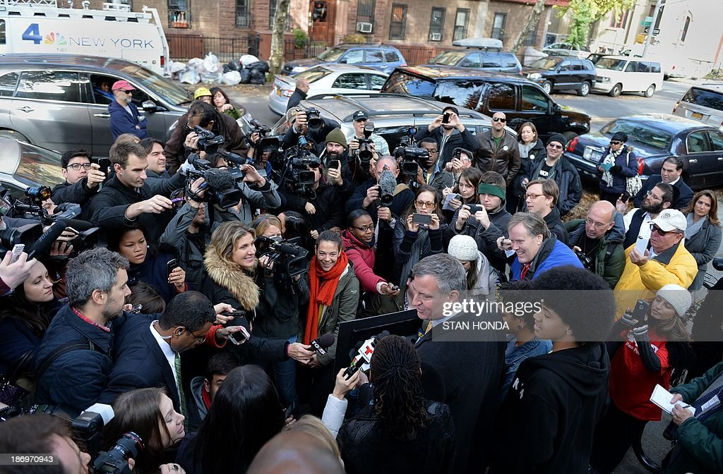 New York City Democratic mayoral candidate Bill de Blasio (C, bottom) speaks with his family after voting at the Park Slope Branch Public Library in the Brooklyn borough of New York November 5, 2013. AFP PHOTO/Stan HONDA