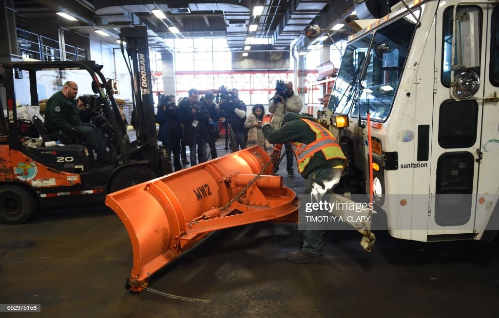 A New York City Department of Sanitation garbage truck is fitted with a snow plow in the west side depot March 13, 2017 to be used over the next two days as the city braces for a nor'easter that could dump as much as two feet of snow on the city. The National Weather Service issued a 24-hour blizzard warning from midnight Monday (0400 GMT Tuesday) for New York, America's financial capital and largest city, stretching north into Connecticut and south into New Jersey. A. CLARY