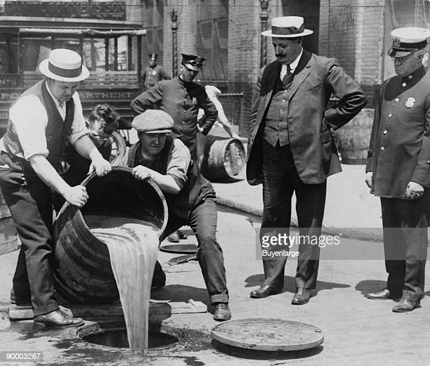 New York City Deputy Police Commissioner John A Leach right watching agents pour liquor into sewer following a raid during the height of prohibition