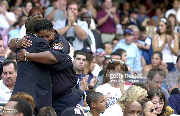 New York City EMT hugs a fellow worshiper at the 'A Prayer For America' memorial service at New York's Yankee Stadium 23 September to remember the...