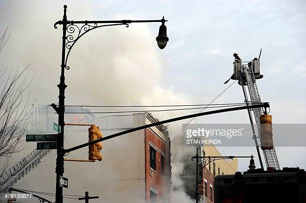New York City Fire Department firefighters at the scene of an explosion and building collapse at Park Avenue and East 116th Street March 12 2014 in...